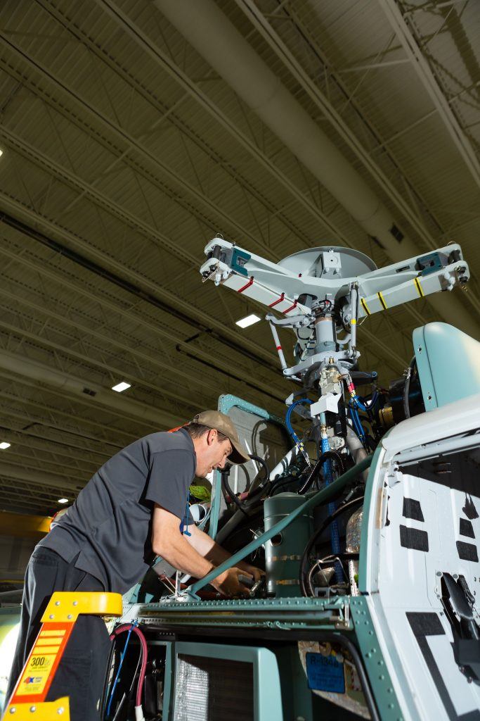 A male employee is working on a helicopter part at an Airbus Helicopters facility in Mississippi